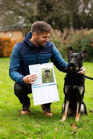 Presenter Rob Bell holding his Metfriendly calendar with a retired police dog